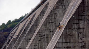 Workers scaled the surfaces of the downstream buttresses to install the geomembrane system.