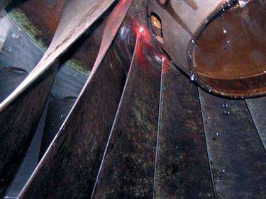Cracking is more typical at the upper fillet of a turbine runner, where the maximum force is transmitted to the shaft. The coloration due to corrosion is an example of the relative corrosion resistance of CA-15, a martensitic stainless steel. An austenitic in the same location would have been spotless.