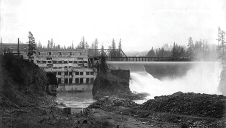 The newly completed River Mill Dam, circa 1911, is surrounded by felled timber at the dam's construction site.