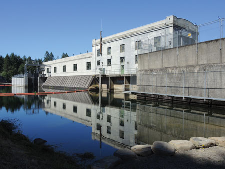 This photo shows River Mill Dam as it is today, with calm waters and the upstream fish collector visible at left. The collector was completed and put into operation in 2012.