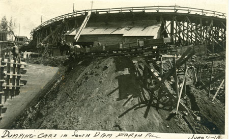Horses pull cars on rails containing earthfill for the facility (circa 1913).