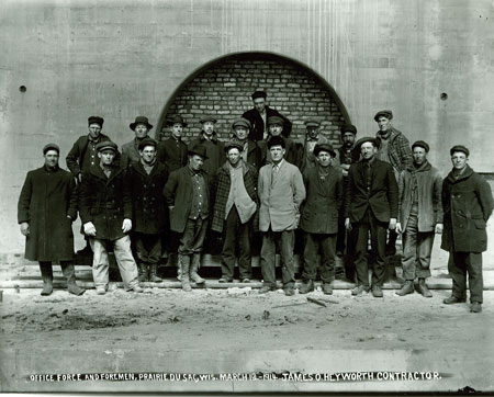 Members of the facility's office force, construction crew and foreman are pictured on site during March 1914.