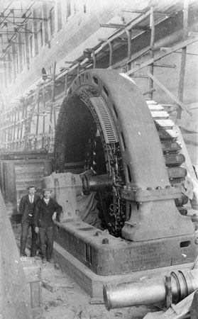 Engineers pose next to the installation of Unit 1 in 1910, the first of 16 horizontal-shaft Francis turbines to be installed at Pointe du Bois.