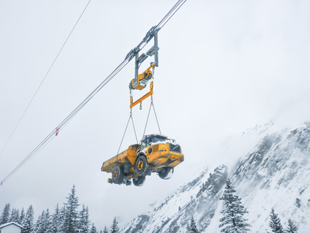 A 20-ton dump truck is being transported via a heavy crane system at the 360-MW Obervermuntwerk II project in Austria during heavy snows in the Alps.